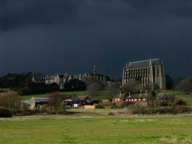 Atmoshpheric photograph of Lancing College brightly lit with storm clouds behind.